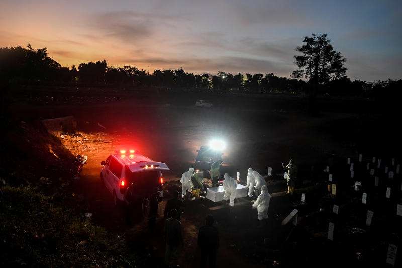 Workers wearing protective suits bury a coronavirus disease victim at Pondok Ranggon cemetery complex in Jakarta on Tuesday. (Antara/Reuters photo)