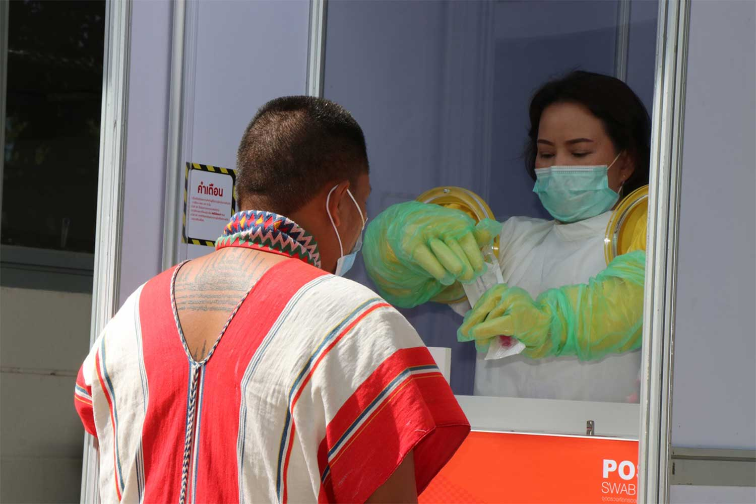 A hospital staffer takes a swab from a migrant at the Covid-19 testing station opened at Kanchanaburi immigration office on Thursday to prevent the spread of coronavirus disease from Myanmar. (Photo: Piyarat Chongcharoen)