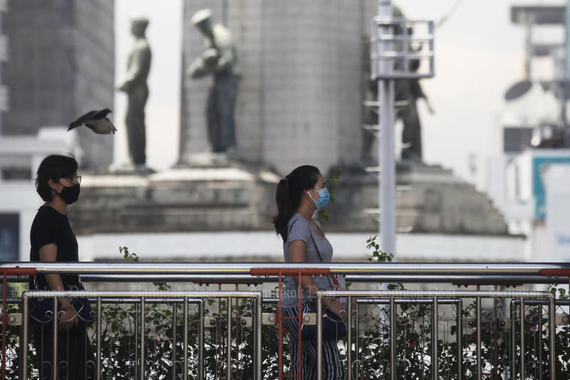 Pedestrians wearing face masks to prevent the Covid-19 walk on an overpass near the Victory Monument on Saturday. The coronavirus outbreak makes people stressful, leading to suicide. (Photo by Nutthawat Wicheanbut)