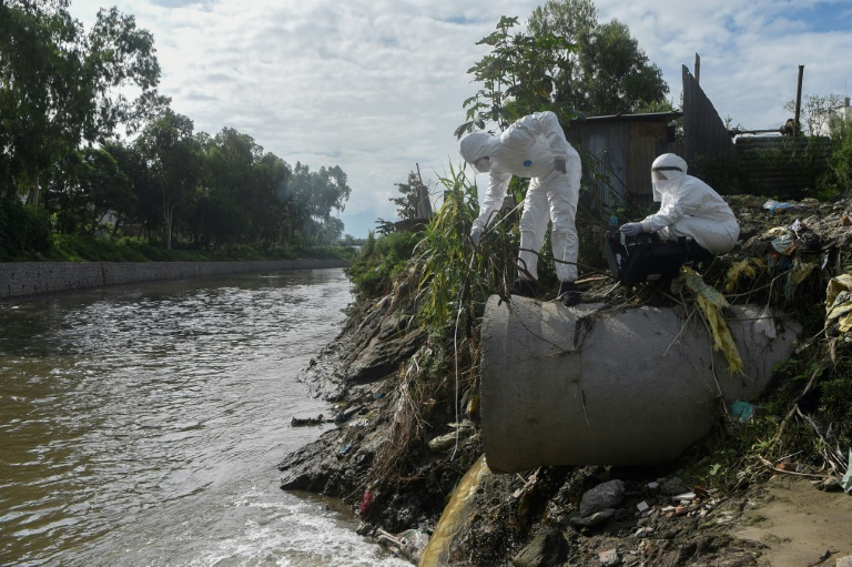 Researchers in Nepal collect samples of sewage dumped into a river to trace the spread of the coronavirus.