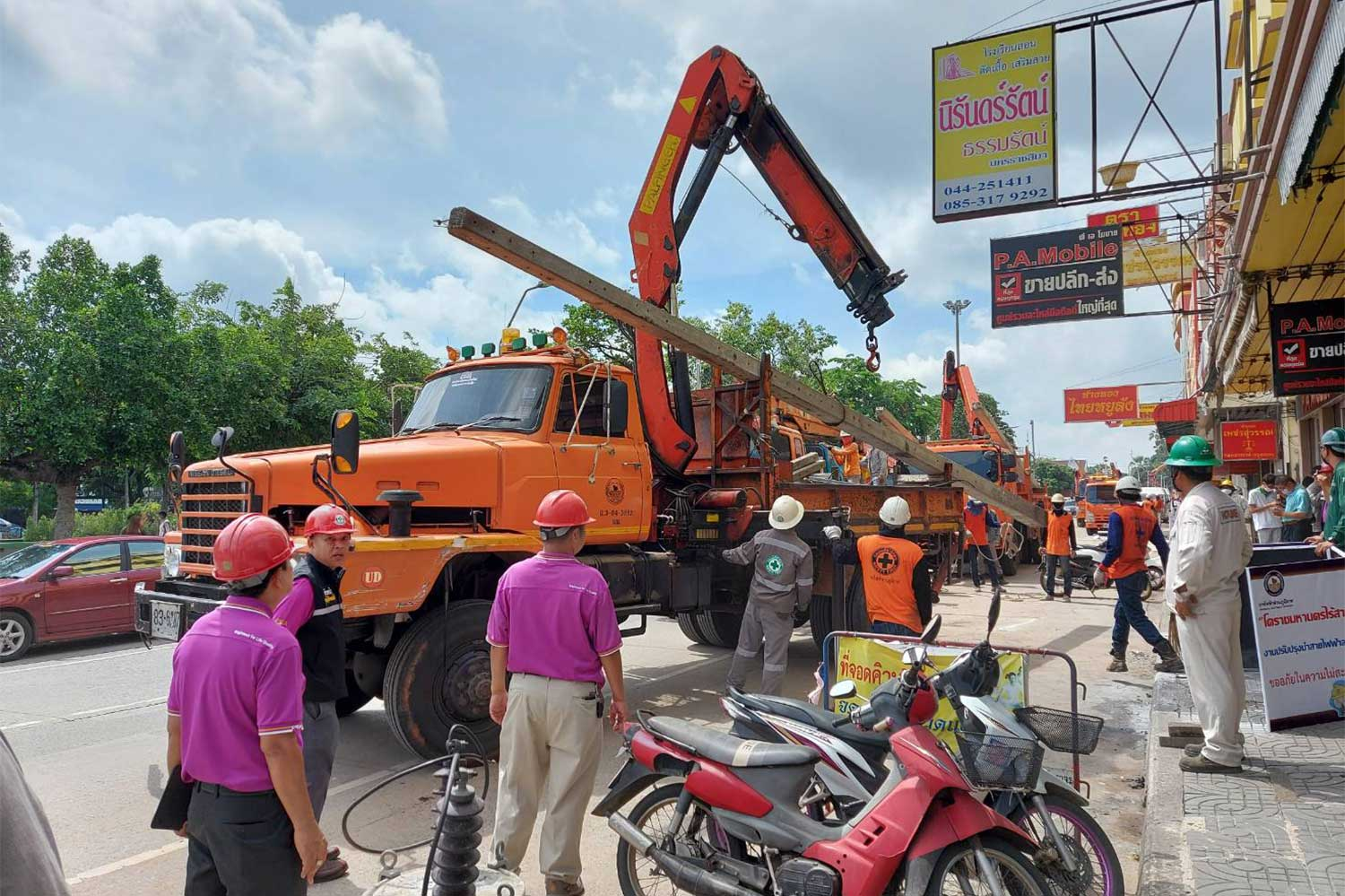 A concrete power pole is lifted onto a truck after Provincial Electricity Authority workers finish moving electrical wires and cables underground in parts of Nakhon Ratchasima on Saturday. (Photo by Prasit Tangprasert)