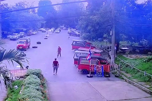 Footage from a surveillance camera shows the back of Sao Puangthong as he and rival  tuk-tuk driver Chaowalit Phuthaksin confront each other during their quarrel outside Hat Yai railway station on Sunday afternooon. (Supplied)