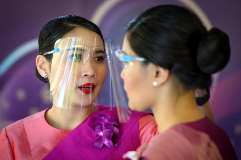 Thai Airways flight attendants wear face shields at a pop-up aeroplane-themed restaurant at the airline's headquarters in Bangkok Sept 10, 2020. The nation's flagship carrier, got court approval for its debt restructuring on Monday. (AFP photo)