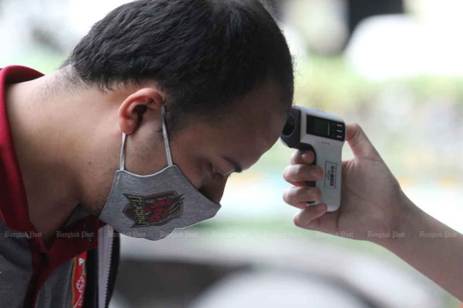 A football fan has his temperature checked before being allowed into PAT Stadium in Klong Toey district, Bangkok, to watch a Thai League football match on Sunday. WICHAN CHAROENKIATPAKUL