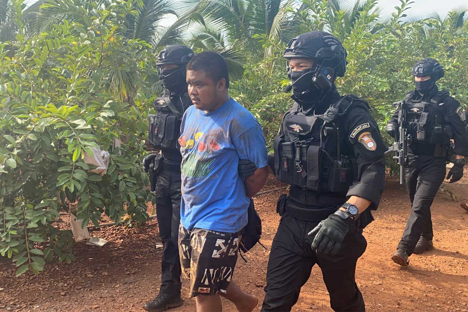 Suspect Arnon Kiram, 21, is caught in a field near his house in Tha Luang district, Lop Buri on Tuesday. (Photo supplied)