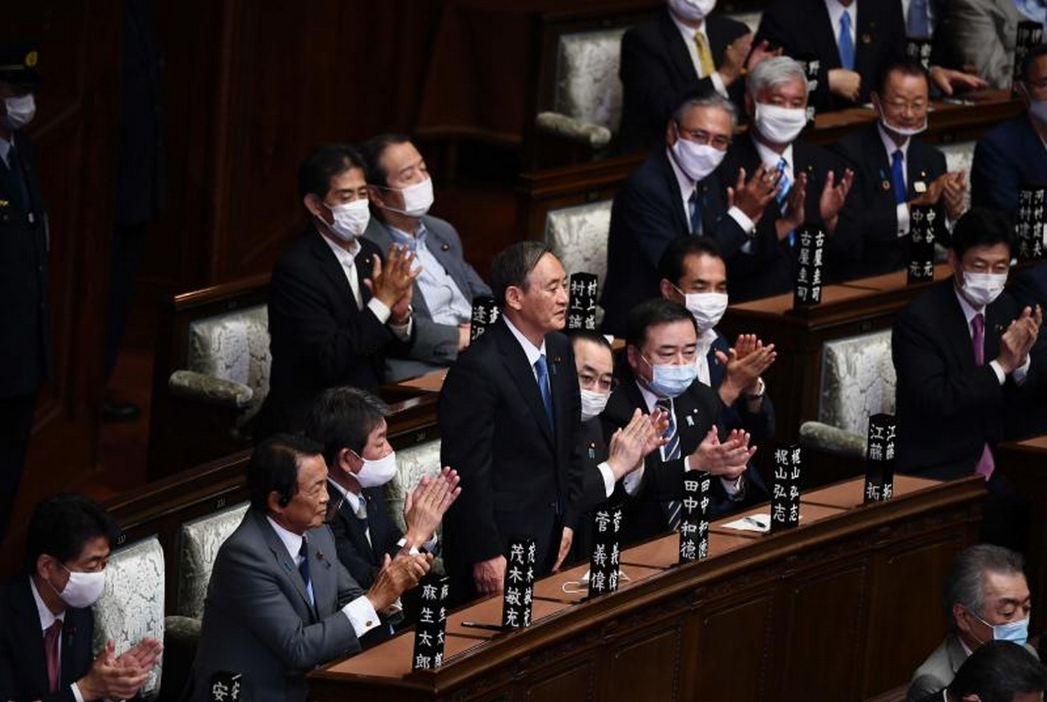 The new leader of Japan's Liberal Democratic Party, Yoshihide Suga (standing), is applauded by outgoing prime minister Shinzo Abe(left) and other government officials after he was elected prime minister by the Lower House of parliament in Tokyo on Wednesday.(Photo: AFP)