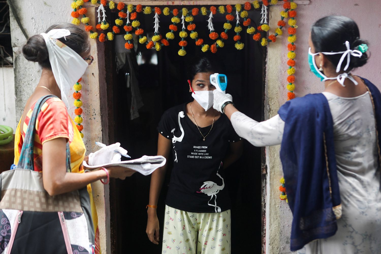 Community health volunteers check the temperature of a girl at a slum area during a checkup campaign for the Covid-19 disease in Mumbai on Wednesday. (Reuters photo)