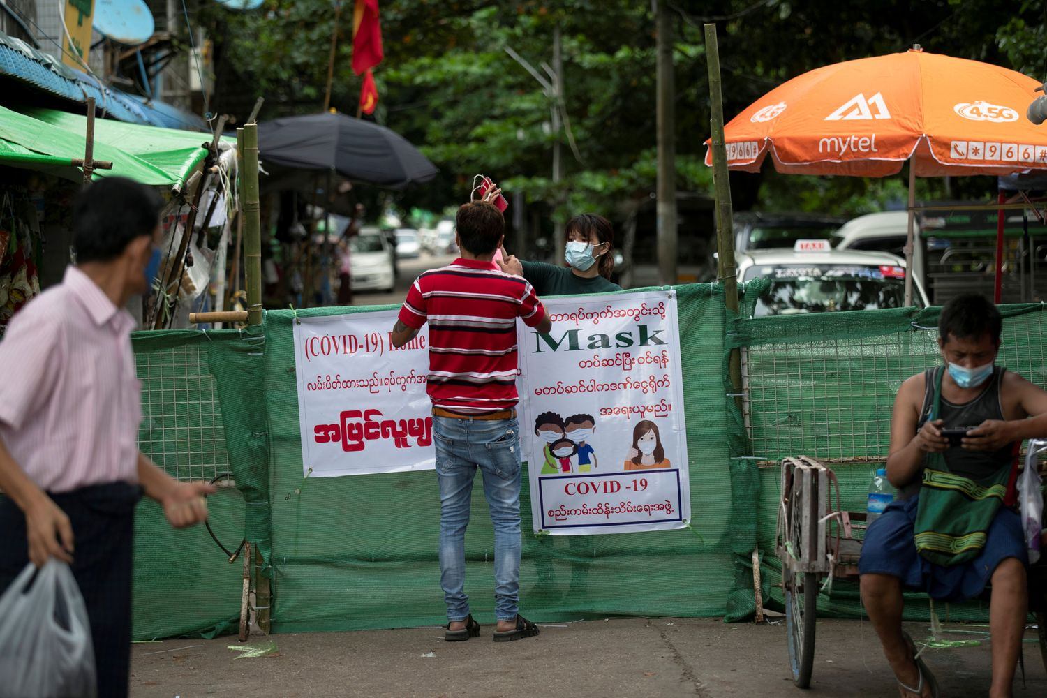 A woman passes a package to a man behind a makeshift barricade, blocking off a street to prevent the spread of Covid-19 in Yangon on Saturday. (Reuters photo)