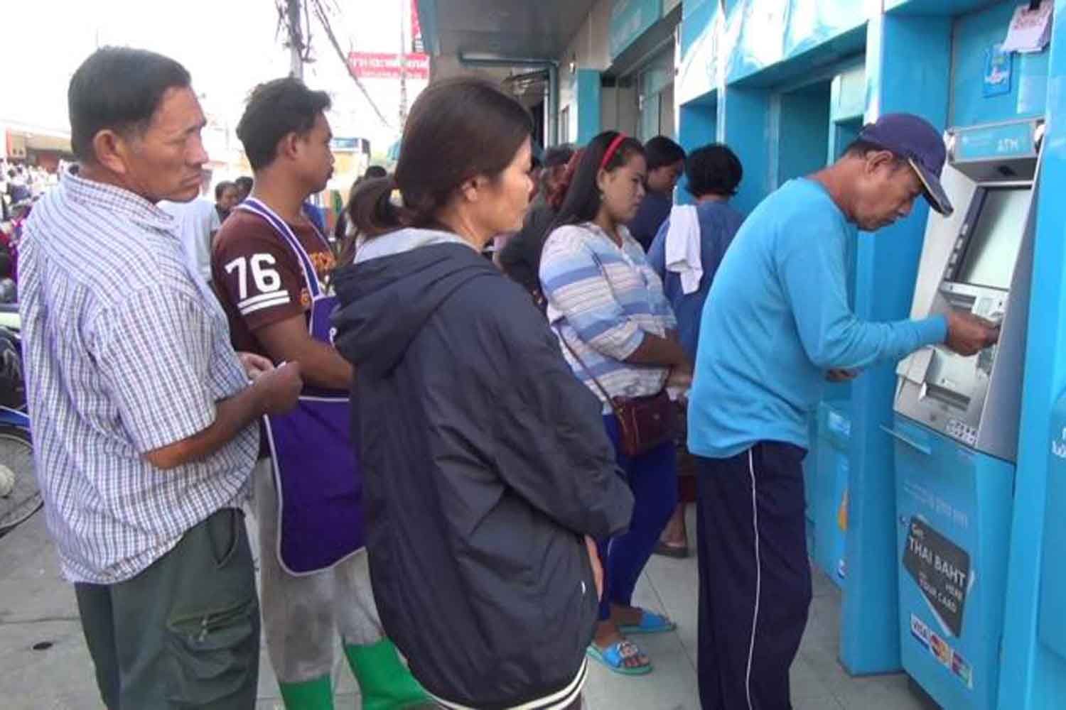 Holders of state welfare cards queue to withdraw money from ATMs in Buri Ram province. The government will increase its financial assistance, to inject more money into the economy. (File photo: Surachai Piragsa)