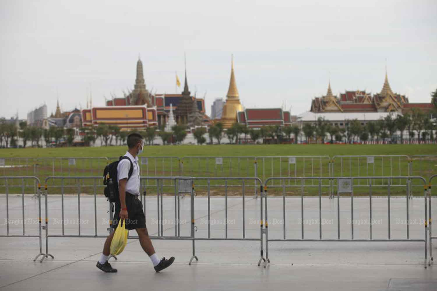 A student walks past Sanam Luang, with the Grand Palace in the background, in Bangkok on Wednesday, when Thailand logged no new Covid-19 cases. (Photo: Nutthawat Wicheanbut)