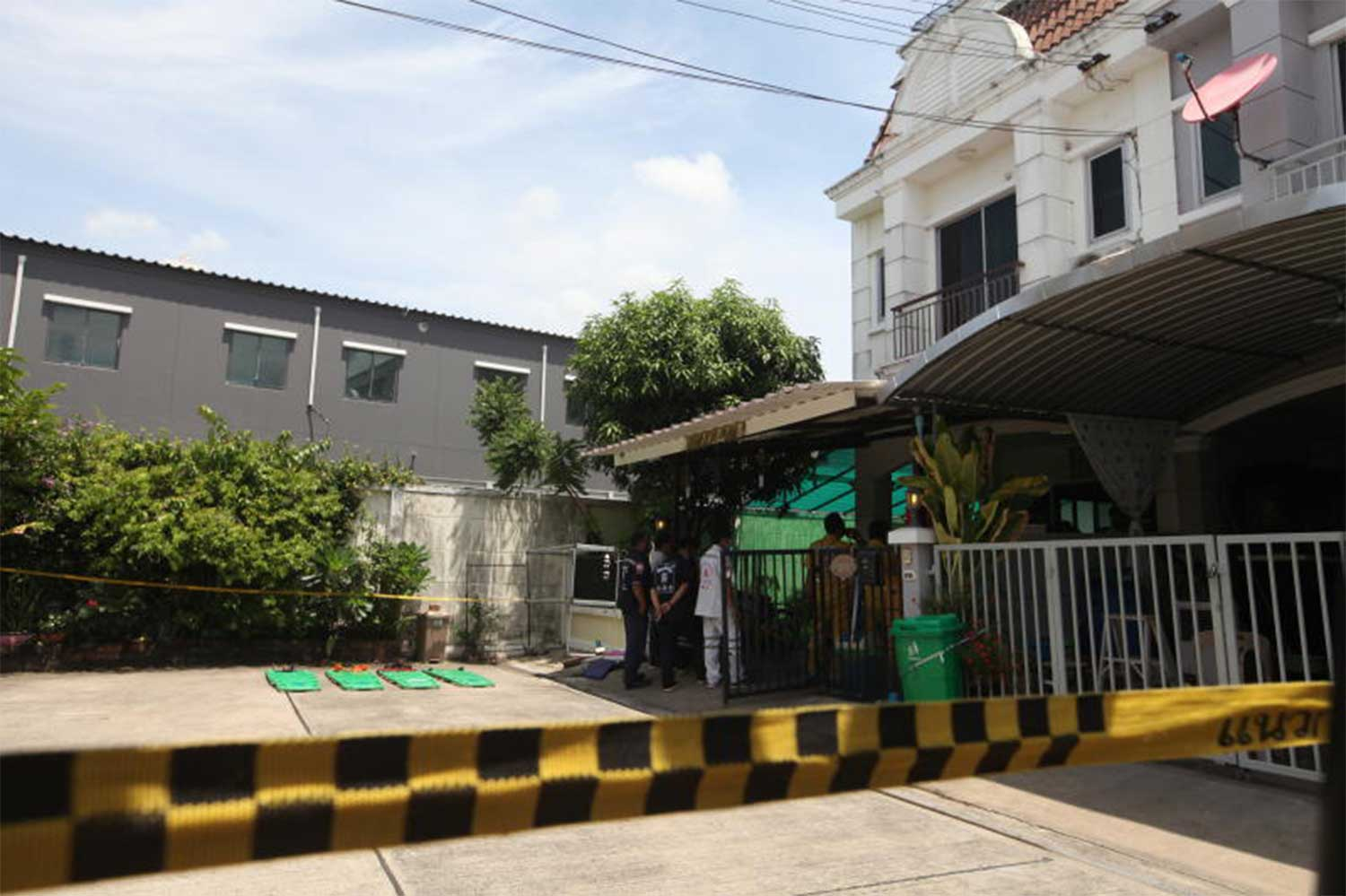 Police cordon off the house where five members of an army sergeant major's family were found shot dead at a housing estate in Thung Khru district, Bangkok, on Thursday morning. (Photo: Arnun Chonmahatrakool)
