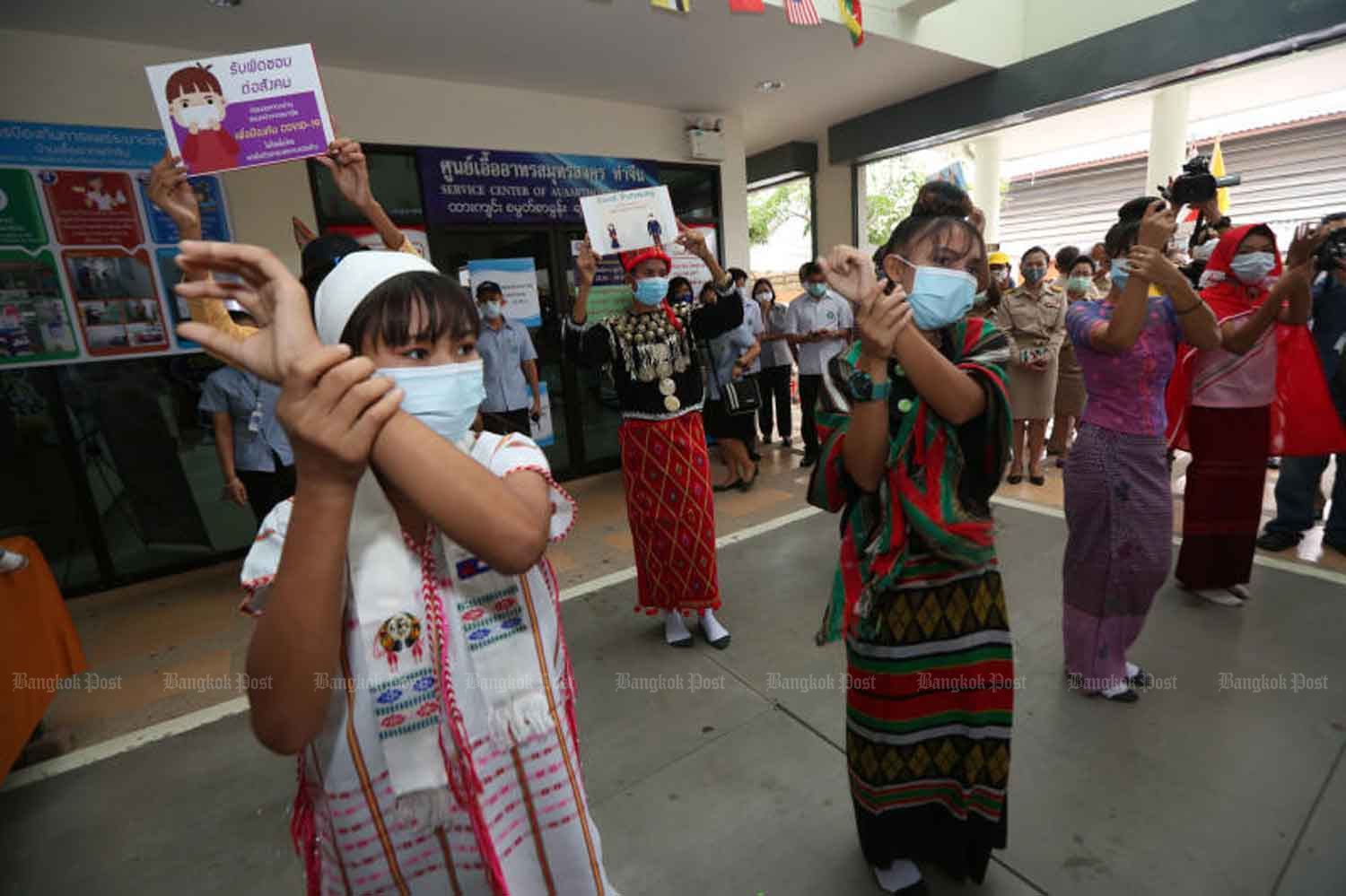 Health volunteers take part in an activity to raise awareness about Covid-19 among migrant labourers in Muang district in Samut Sakhon in April. Health officials are investigating the case of a Covid-infected Myanmar girl who was confirmed with the disease after returning from Thailand early this month. (Photo: Varuth Hirunyathep)
