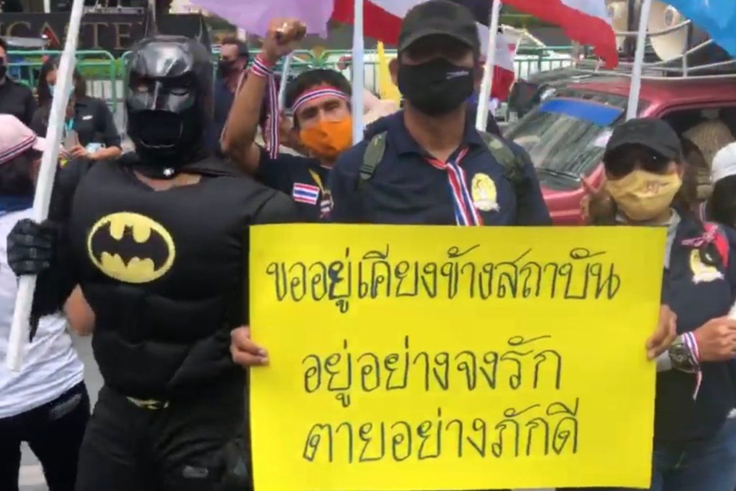 A protester shows a poster that reads: 'We stand by the institution. Live with love. Die loyal' during a rally to urge Thanathorn Juangroongruangkit to leave the country in front of the Thai Summit building in Bangkok on Thursday. (Photo from Twitter@queenblackspade)