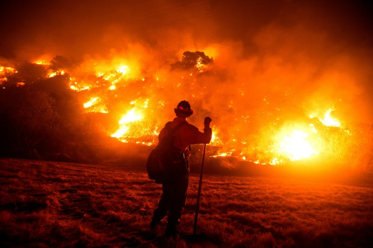 A firefighter works at the scene of the Bobcat Fire burning on hillsides near Monrovia Canyon Park in Monrovia, California on Tuesday.