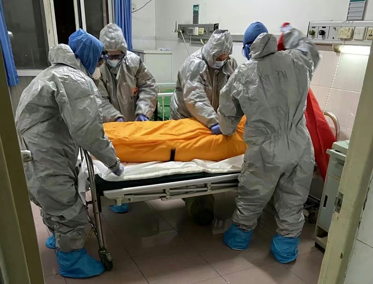 Medical workers prepare to take away the body of Covid-19 victim Zhang Lifa, the father of Zhang Ha, at a hospital in Wuhan, China on Feb 1. (Photo: AFP)