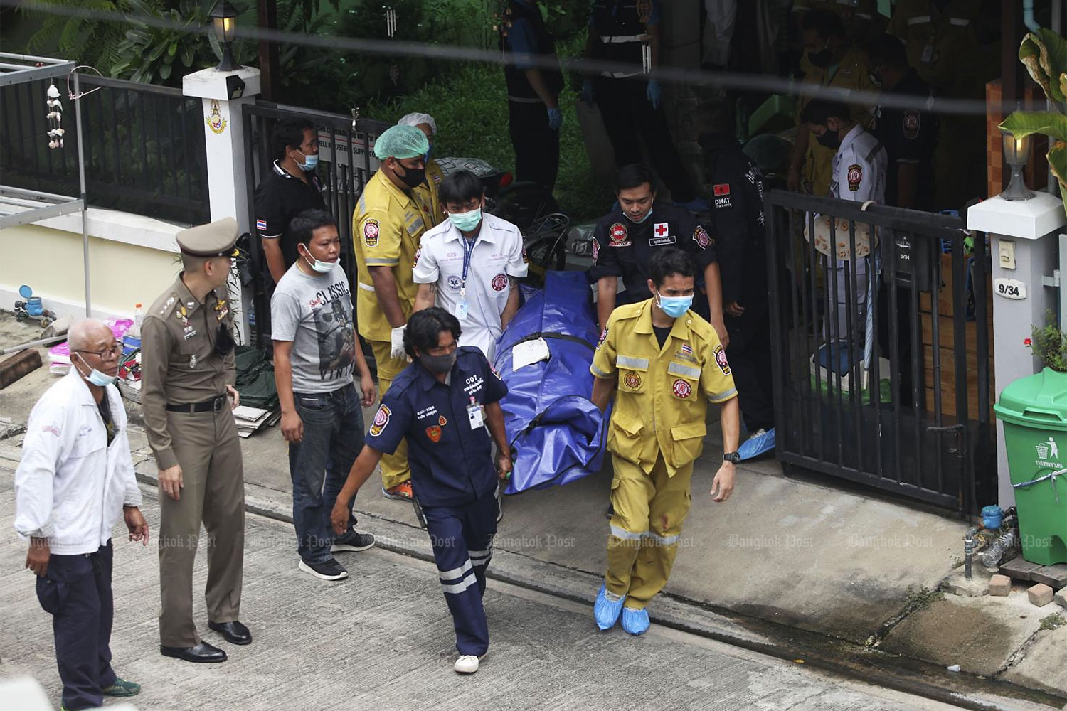 Rescue workers remove a body from a house in Bangkok's Thung Khru district where a former soldier is believed to have shot dead four family members before taking his own life yesterday morning.(Photo by Arnun Chonmahatrakool)