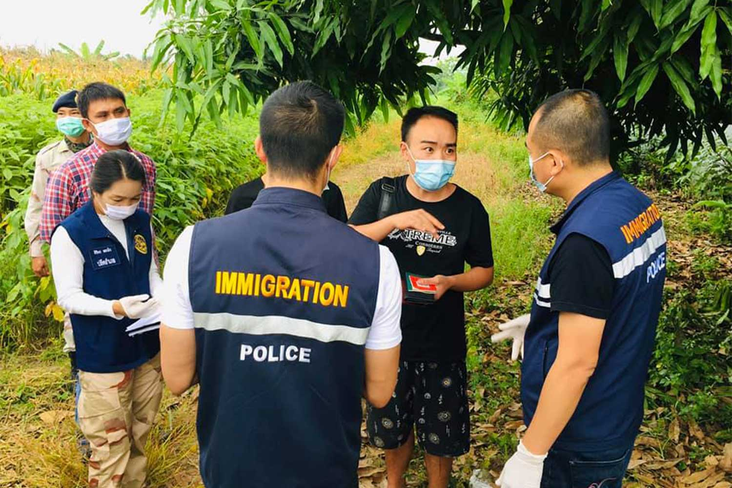 Immigration police question one of the two Chinese men caught after crossing the Moei River from Myanmar into Mae Sot district, Tak province, on Friday morning. (Photo: Assawin Pinitwong)