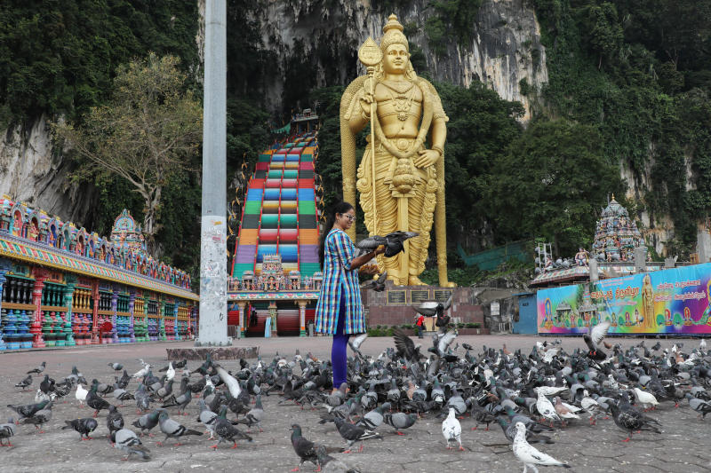 A woman feeds pigeons at Batu Caves, during the coronavirus outbreak in Malaysia, on July 15, 2020. (Reuters file photo)