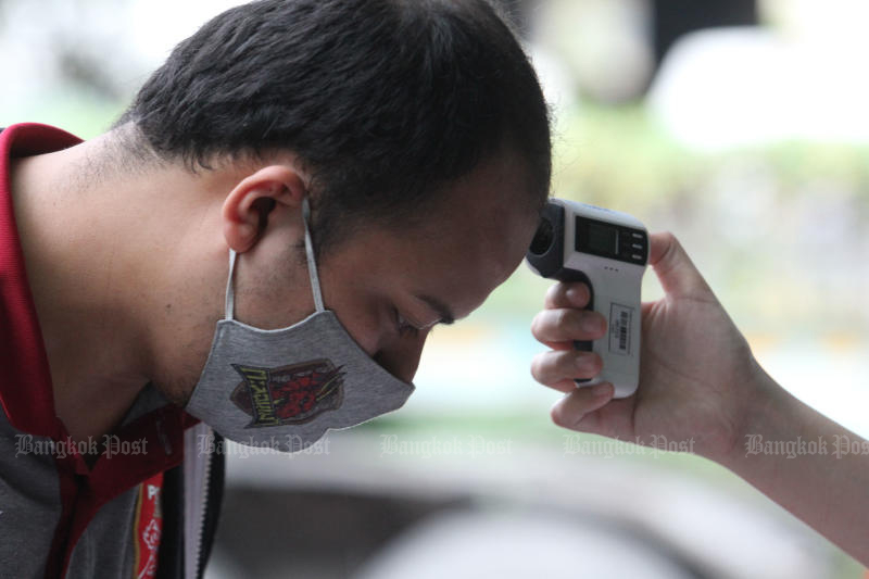 A football fan has his body temperature checked for signs of Covid-19 disease before being allowed into the PAT Stadium on Saturday. Thailand on Friday logged its 59th fatality from the disease, the first since June 2. (Photo: Wichan Charoenkiatpakul)