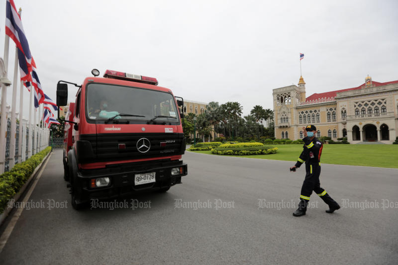 A worker walks toward one of the seven fire engines that will be on standby at Government House to prepare for a rally that protesters intend to stage on Sunday. (Photo by Chanat Katanyu)