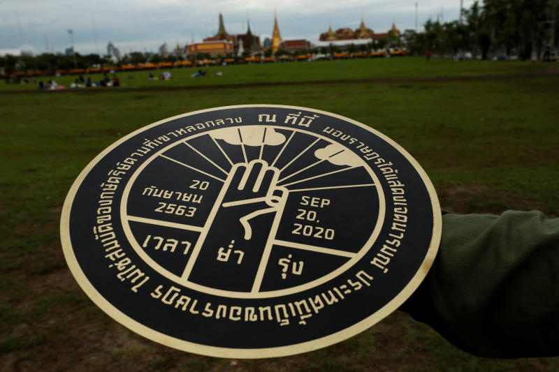 A student holds a replica of the plaque installed by student leaders at Sanam Luang on Sunday morning. (Reuters photo)