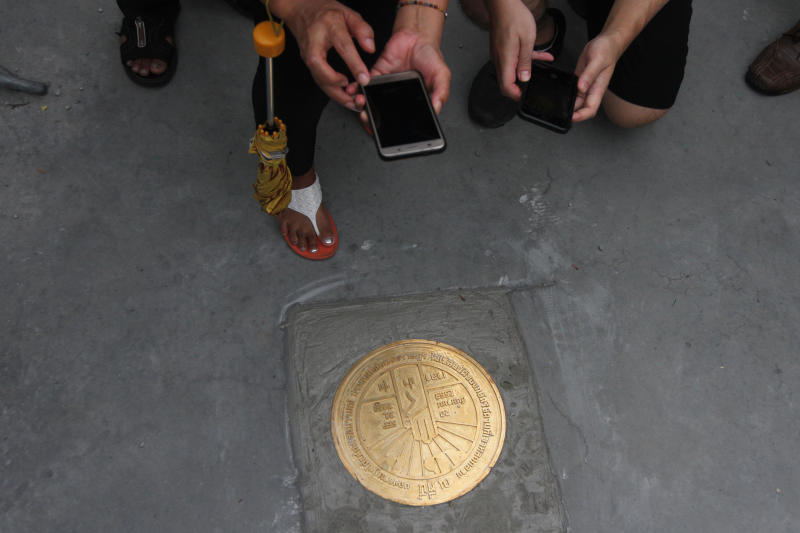 A protester takes a picture of a new plaque after it was installed at Sanam Luang on Sunday. (Photo by Wichan Charoenkiatpakul)