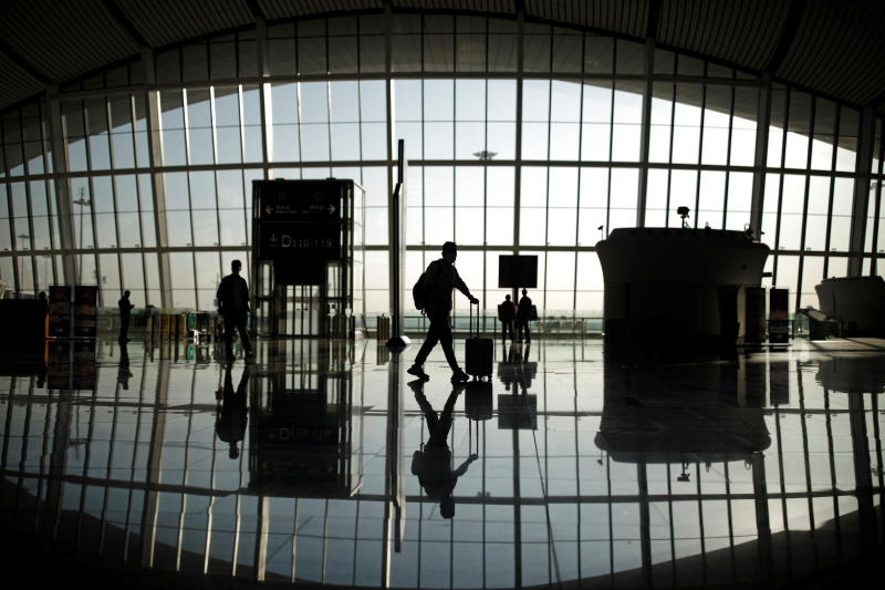 Travellers are seen silhouetted at Beijing Daxing International Airport in Beijing on Saturday. (Reuters photo)