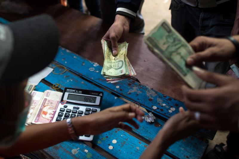 This photo taken on July 6, 2017 shows migrant workers changing money from Thai baht to Myanmar kyat at the Myanmar imigration office in Myawaddy. (AFP)