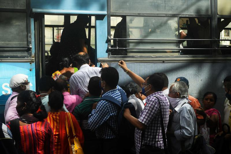 Commuters rush to catch a public bus without maintaining social distancing despite fears over the spread of the Covid-19 coronavirus, in Kolkata on Monday. (AFP photo)