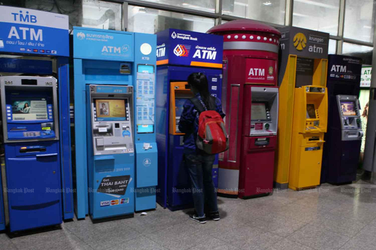 A bank customer uses an ATM in Bangkok. The Anti-Money Laundering Office is verifying a report that suspicious money transactions passed through several Thai banks. (Bangkok Post file photo)