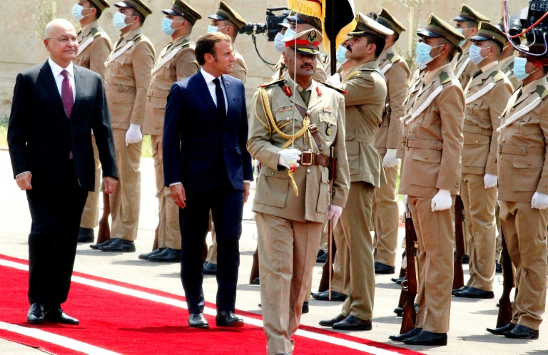 Iraq's President Barham Saleh, who is warning of risks to his country, inspects an honor guard as he welcomes French President Emmanuel Macron (left) on September 2, 2020