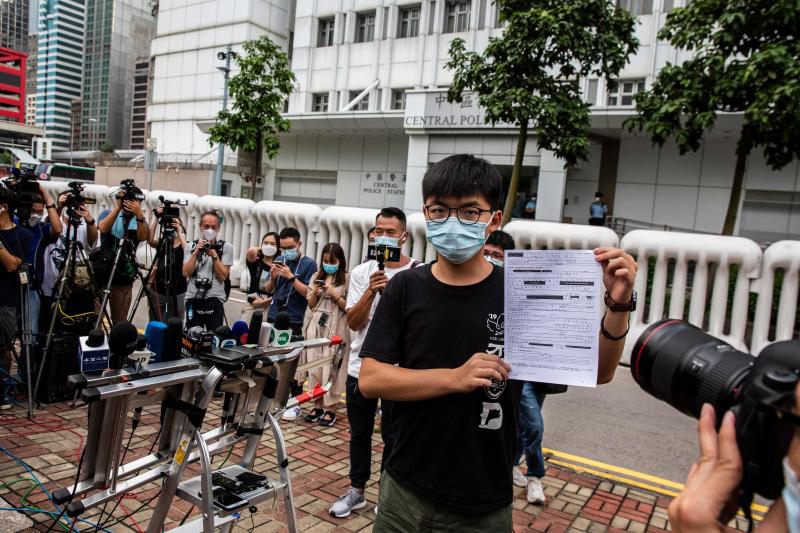 Joshua Wong speaks to the media while holding up a bail document after leaving Central police station in Hong Kong on Thursday, after being arrested for unlawful assembly related to a 2019 protest against a government ban on face masks. (AFP photo)
