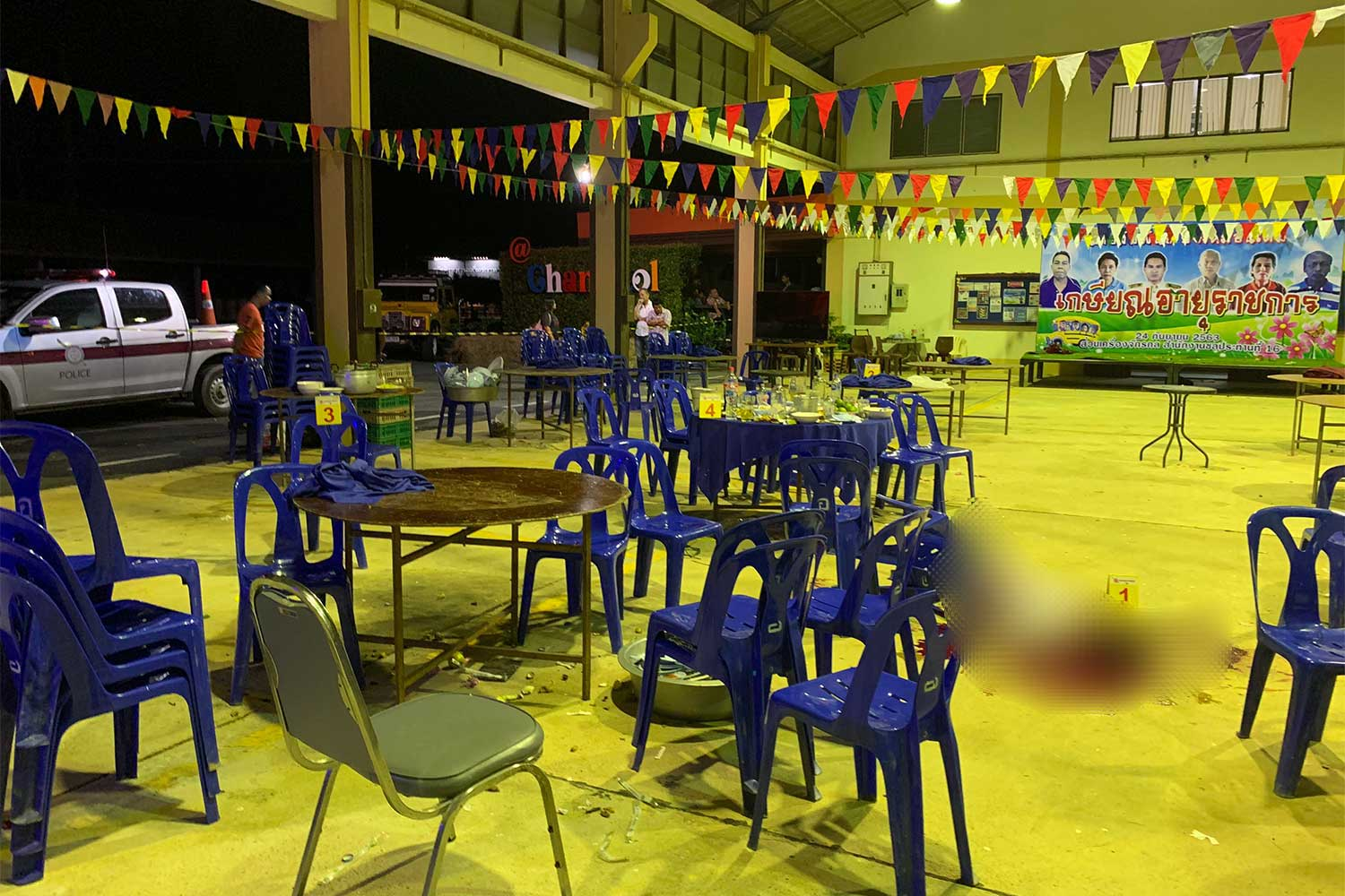 The body of the slain official (blurred) lies on the floor at the venue for the retirees' farewell party at the 16th Irrigation office in Hat Yai district, Songkhla, early on Friday morning. The sole suspect, an inebriated office driver, was waiting to surrender to police when they arrived. (Photo: Assawin Pakkawan)