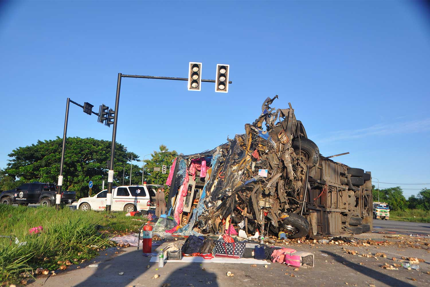 Rescue workers try to retrieve injured and dead victims from a double-decker tour bus that overturned after ramming into a trailer truck in Muang district of Nakhon Ratchasima early Saturday. (Photo: Prasit Tangprasert)