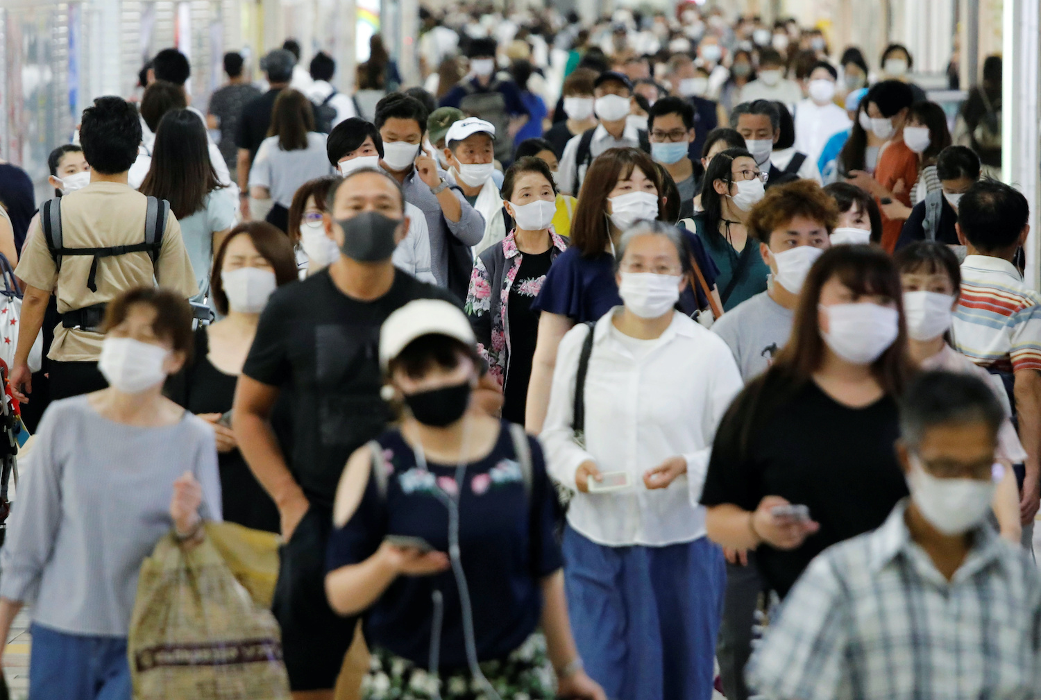 Commuters walk through a train station in Tokyo. (Reuters Photo)