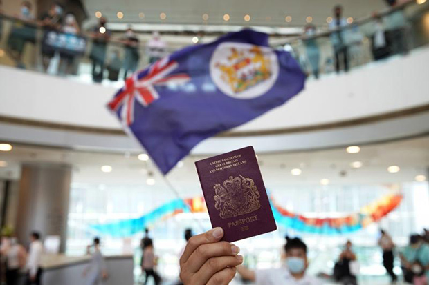 A protester holds a British National Overseas  passport during a lunch-hour rally in Hong Kong. (South China Morning Post photo)