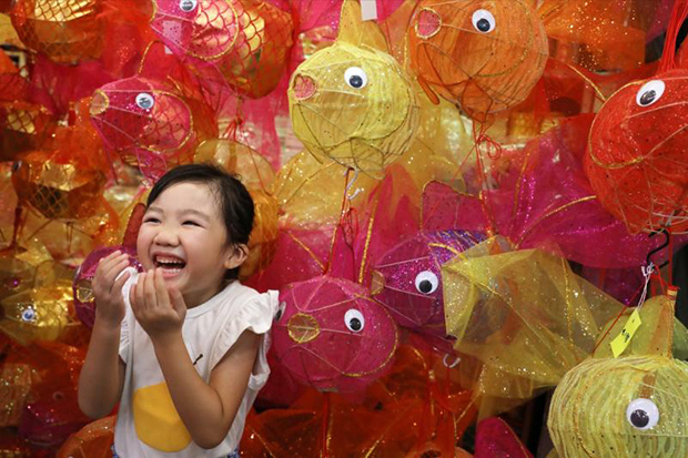 A Hong Kong girl poses for a photo with fish-themed lanterns crafted for this year's Mid-Autumn Festival. (South China Morning Post photo)
