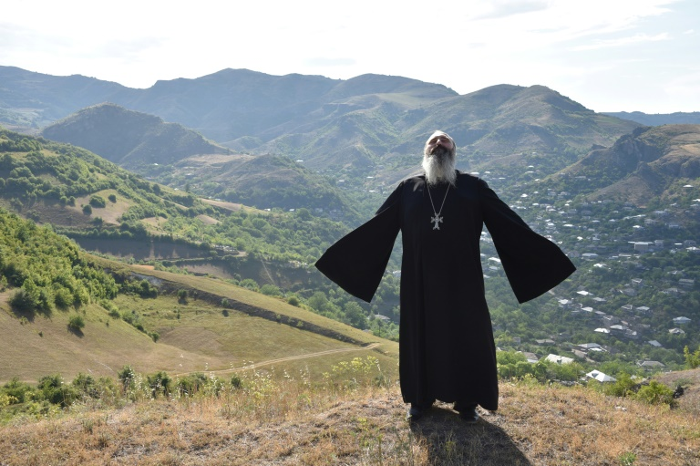 Priest Ter Abel prays for peace outside the village of Movses on the Armenian-Azerbaijani border on July 15, 2020.
