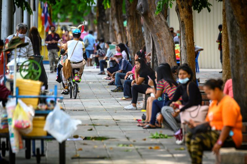 Unemployed people sit on the side of a major street in Bangkok on Sept 15, 2020. (AFP photo)