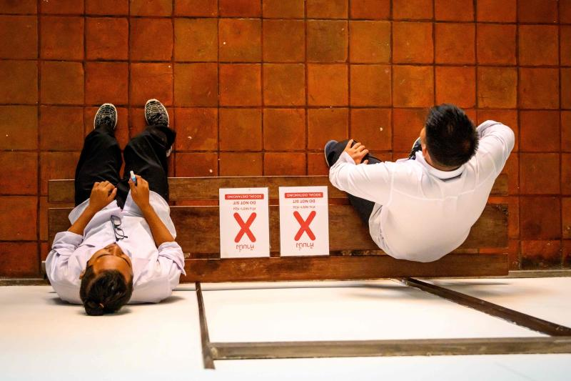 Students rest on a bench marked for social distancing to prevent the spread of the Covid-19 novel coronavirus at the National Museum in Bangkok on Aug 14, 2020. (AFP file photo)