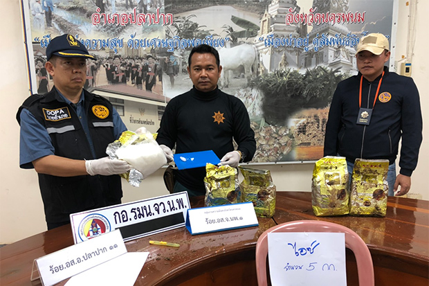 District officials show the five packages containing crystal methamphetamine, or ice as the handwritten sign says, found in Pak Pla district of Nakhon Phanom province on Monday morning. (Photo: Pattanapong Sripiachai)