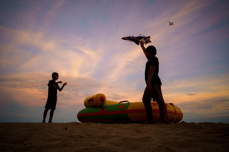 Children fly a kite at Cha-am beach in Cha-am district of Phetchaburi province on Saturday. The Covid-19 panel extended the emergency decree for another month ahead of the government allowing some tourists to enter the kingdom. (Reuters photo)