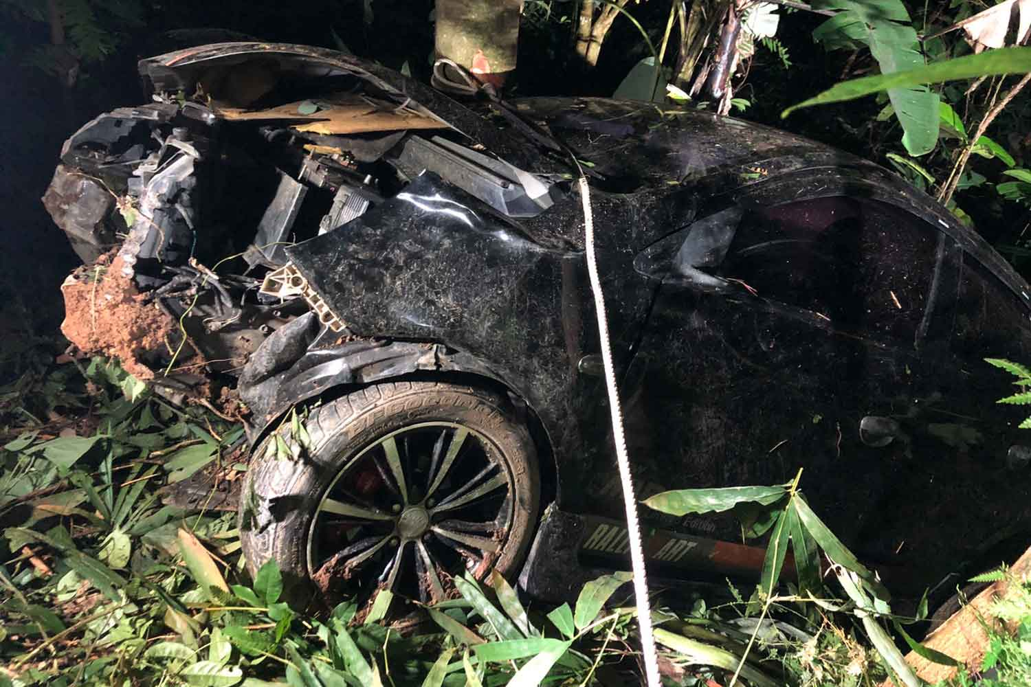 The Mitsubishi Mirage car after it a plunged into a ravine from the main highway in Na Mom district of Songkhla province early on Monday night. The driver had only minor injuries and did not bother to wait around for police. (Photo: Assawin Pakkawan)