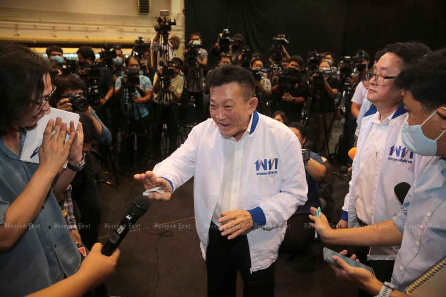 Re-elected Pheu Thai Party leader Sompong Amornvivat greets reporters at the party's headquarters in Bangkok on Thursday. (Photo: Chanat Katanyu)