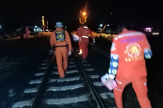 Rescue volunteers attend the scene where a man was killed by a train in Huay Thalaeng district of Nakhon Ratchasima on Sunday. (Photo by Prasit Tangprasert)