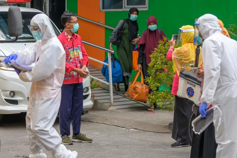People infected with the Covid-19 novel coronavirus (centre) carry their belongings as they are moved from a health centre in Jakarta on Oct 1, 2020, to a special hospital to be isolated as a measure to reduce the spread of the virus. (AFP)