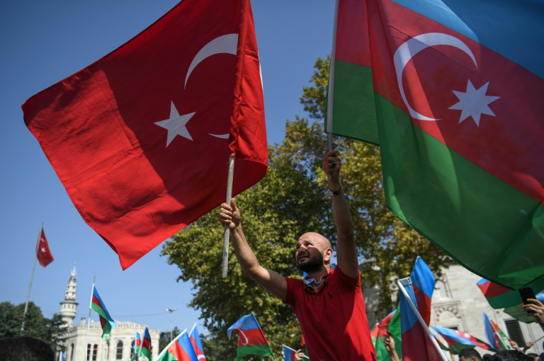 An Azeri protester waves Azerbaijani and Turkish national flags in a demonstration in Istanbul on Sunday