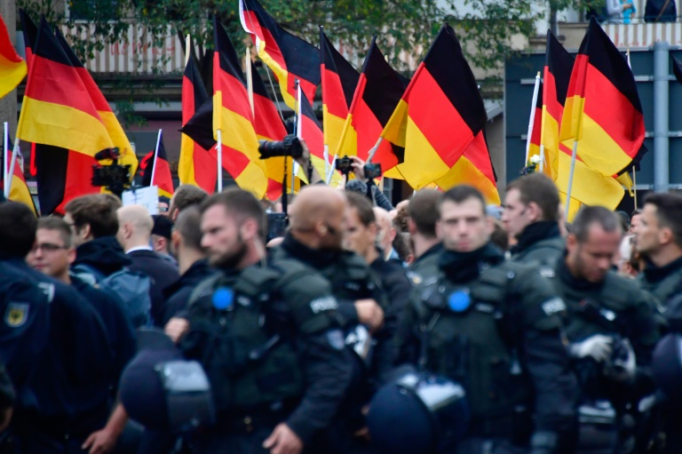 Supporters of the far-right AfD party wave German flags as they walk behind a barrage of riot police during a demonstration.