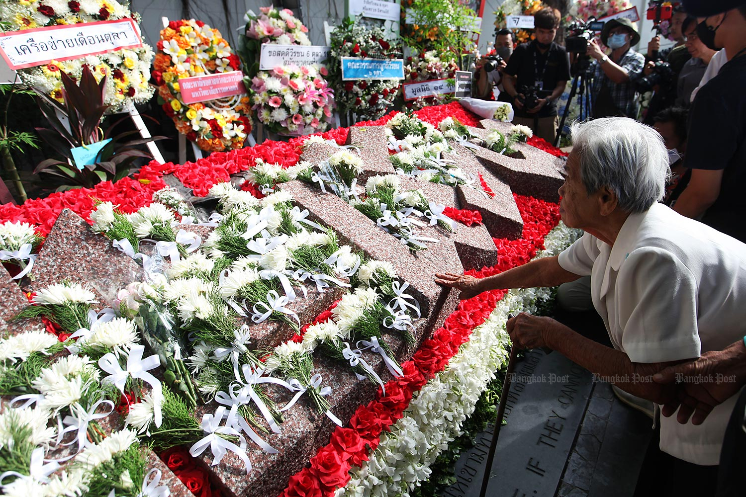 Relatives of people killed in the Oct 6, 1976 massacre at Thammasat University lay flowers at the Historical Sculpture Park at the university's Tha Prachan campus on Tuesday, marking the 44th anniversary of the bloodshed.(Photo by Arnun Chonmahatrakool)