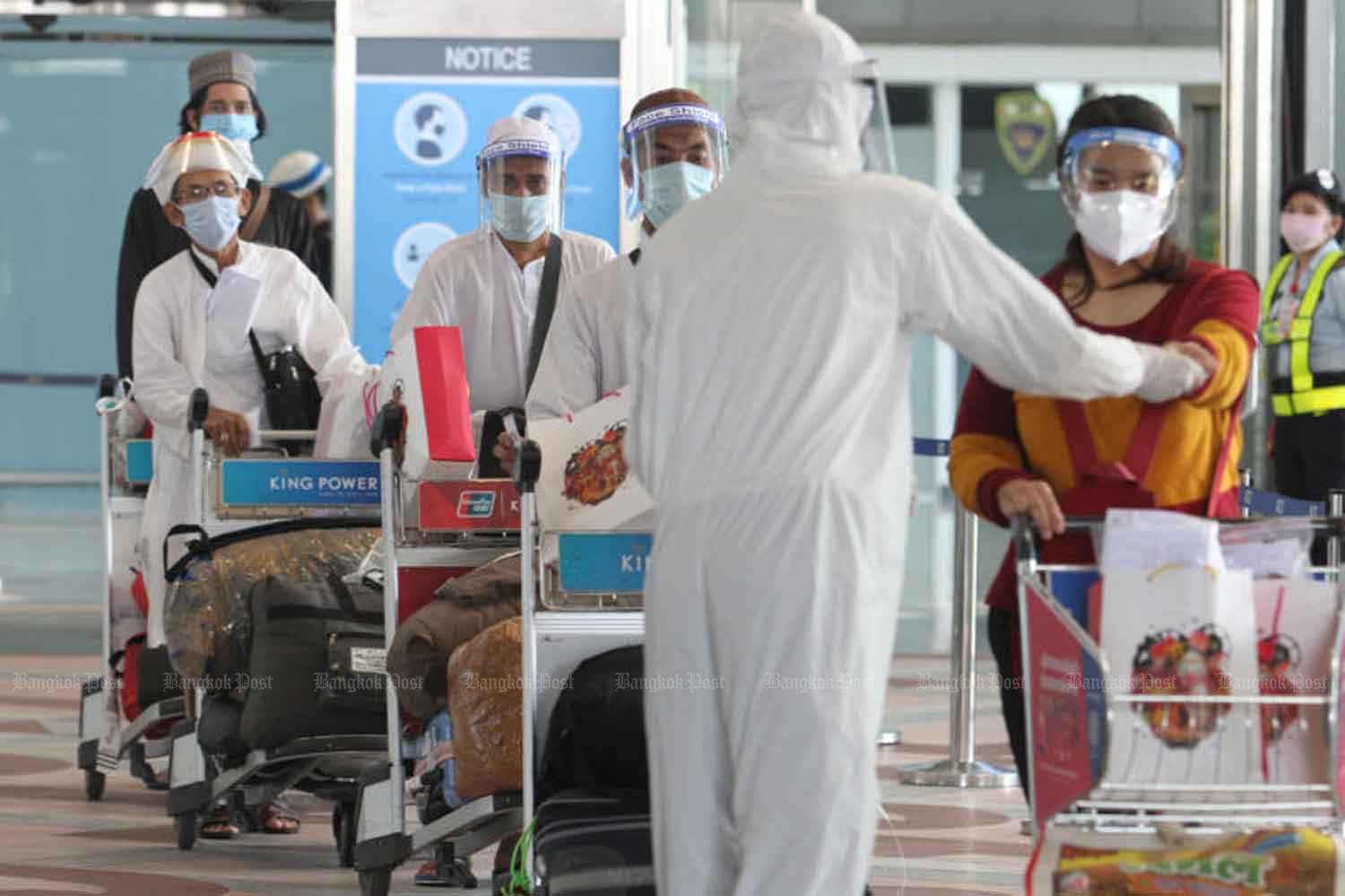 Disease control staff examine returnees at Suvarnabhumi airport. The government reported 15 new Covid-19 cases, all returnees, on Wednesday. (Bangkok Post file photo)
